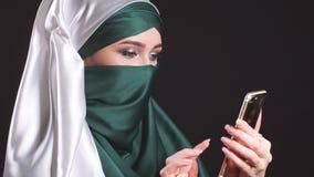 Portret van Mooi Arabisch Moslimmeisje die Mobiele Telefoon met behulp van stock footage