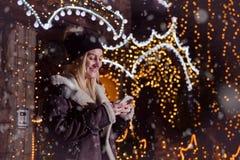 Portret van mooi blonde glimlachend meisje die slimme telefoon in F met behulp van stock afbeelding