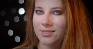 Portret van mooi blondemodel met het heldere samenstelling letten op in camera met geheimzinnige glimlach op bokehachtergrond stock videobeelden