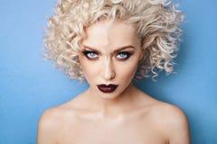 Portret van mooi, fasionable en modieus modelmeisje met verbazende blauwe ogen, krullend blondehaar en met professionele heldere  stock afbeelding