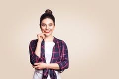 Portret van mooi gelukkig meisje die in toevallige stijl camera met toothy glimlach bekijken Studio op beige achtergrond wordt ge stock fotografie