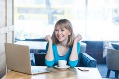 Portret van mooi gelukkig tevreden positief jong meisje freelancer met blondehaar in blauwe t-shirtzitting in koffie en stock foto's