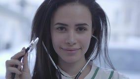 Portret van mooi glimlachend meisje dicht omhoog Jonge donkerbruine vrouw die met lang haar in de cameraholding kijken stock video