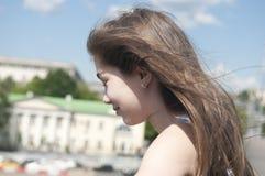 Portret van mooi jong meisje met blazend haar in wind op de achtergrond van de stads blauwe hemel Stock Foto's