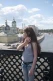 Portret van mooi jong meisje op de achtergrond van de brug blauwe hemel met blazend haar in wind Stock Foto's