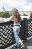 Portret van mooi jong meisje op de achtergrond van de brug blauwe hemel met blazend haar in wind Royalty-vrije Stock Afbeeldingen