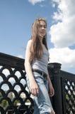 Portret van mooi jong meisje op de achtergrond van de brug blauwe hemel met blazend haar in wind Royalty-vrije Stock Fotografie
