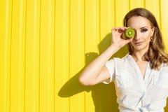 Portret van mooi jong model met lang haar en provocatieve artistieke samenstelling die haar oog achter het gespleten kiwifruit ve Stock Afbeelding