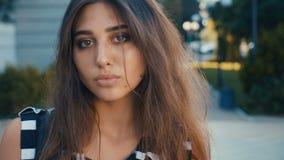 Portret van mooi jong vrouwen donkerbruin model die de camera op een achtergrond van de stadsstraat bekijken Meisje met grote oge stock video
