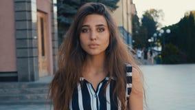 Portret van mooi jong vrouwen donkerbruin model die de camera op een achtergrond van de stadsstraat bekijken Meisje met grote oge stock videobeelden