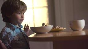 Portret van mooi kind die ontbijt hebben thuis Het kind in de keuken bij lijst het eten Lachend leuk kind stock footage