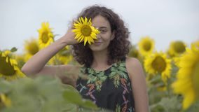 Portret van mooi krullend meisje die de camera bekijken die en haar oog glimlachen behandelen met weinig zonnebloem in stock footage