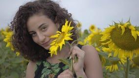 Portret van mooi krullend meisje die jokingly grote zonnebloem op het zonnebloemgebied bijten Verbinding met aard landelijk stock videobeelden