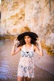 Portret van mooi Latijns meisje op het strand met de zwarte keurige oceaan van de hoedenglimlach en rotsen op de zomerroeping Royalty-vrije Stock Fotografie