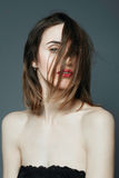 Portret van mooi meisje in de studio met rode lippenstift op een grijze achtergrond Royalty-vrije Stock Foto's