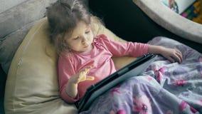 Portret van mooi meisje, een kind dat op de bank onder de deken ligt en op tabletcomputer speelt stock footage