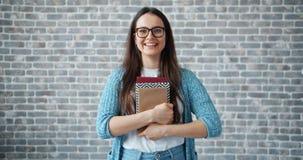 Portret van mooi meisje in glazen die boeken houden en op baksteenachtergrond glimlachen stock footage