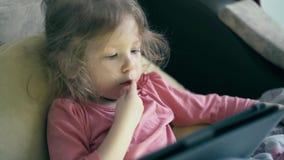 Portret van mooi meisje, kind dat op de bank onder de deken ligt en op een tabletcomputer speelt stock video