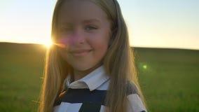 Portret van mooi meisje met blondehaar die bij camera, gebied met zonsondergang op achtergrond glimlachen, gelukkig en blij stock video