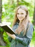 Portret van mooi meisje met boek in park Stock Foto's
