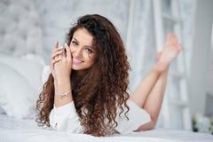 Portret van mooi meisje met krullend haar op het bed Royalty-vrije Stock Foto