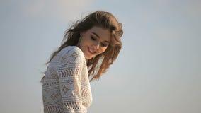 Portret van mooi meisje tegen een blauwe hemelachtergrond stock videobeelden
