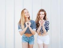 Portret van mooi modieus meisje twee in denimborrels en gestreepte T-shirts die hartvorm met handen tonen outdoors Ha stock fotografie