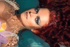 Portret van mooi roodharig meisje in het water Stock Foto
