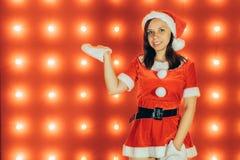Portret van mooi sexy meisje die Santa Claus-kleren op rode achtergrond dragen stock afbeeldingen