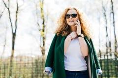 Portret van mooi wijfje met pluizig blondehaar die op celtelefoon aan haar vriend, gelukkig en opgewekte statusaga die eruit zien stock foto
