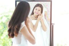 Portret van mooie Aziatische bruid gezet op oorring die in mirr kijken stock foto's