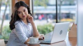 Portret van mooie Aziatische jonge glimlachende vrouwelijke toevallige onderneemster of student van freelancer stock videobeelden