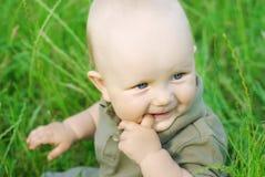 Portret van mooie babyjongen op een gras Stock Foto