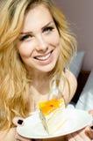 Portret van mooie blonde jonge dame die pret hebben die het alleen grote fruit romige cake gelukkige glimlachen eten & camera bek Stock Fotografie