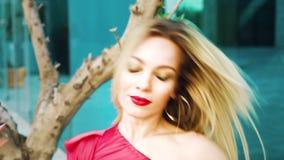 Portret van mooie blondevrouw die met rode lippenstift camera en het dansen bekijken stock video