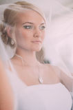 Portret van mooie bruid met maniersluier het stellen thuis bij Stock Afbeeldingen