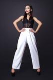 Portret van mooie donkerbruine vrouw in een zwarte blouse en een witte broek, Het schot van de manierfoto Stock Foto