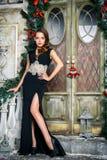Portret van mooie elegante jonge vrouw in schitterende avondjurk over Kerstmisachtergrond Stock Fotografie