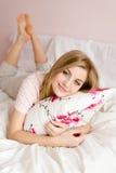 Portret van mooie gelukkige jonge blonde vrouw die pret het ontspannen in bed met bloemen in hand hoofdkussen en het gelukkige gl stock fotografie