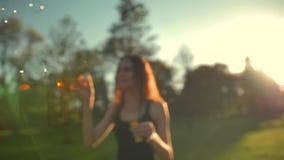 Portret van mooie gember jonge vrouw Blazende bel in het park stock footage