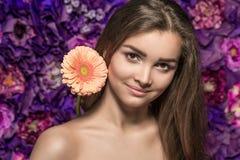 Portret van mooie glimlachende jonge vrouw met een bloemgerbera op de achtergrondmuurbloem Stock Foto's