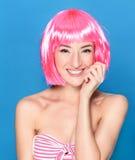 Portret van mooie glimlachende jonge vrouw met roze haar op een blauwe achtergrond royalty-vrije stock fotografie