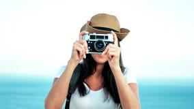 Portret van mooie glimlachende jonge vrouwelijke reiziger in hoed die foto nemen die retro camera met behulp van stock footage
