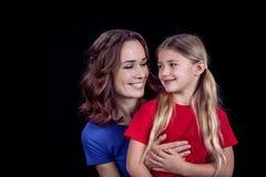 Portret van mooie glimlachende moeder en dochter die elkaar bekijken stock afbeeldingen