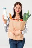 Portret van mooie het glimlachen vrouwenholding het winkelen document zak met organisch vers die voedsel op witte achtergrond wor Royalty-vrije Stock Foto