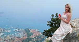 Portret van mooie jonge blonde vrouw met wind die in haar haarzitting blazen op een rots stock footage