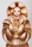 Portret van mooie jonge blondevrouw in de bontjas van de luxevos stock foto's
