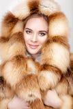 Portret van mooie jonge blondevrouw in de bontjas van de luxevos royalty-vrije stock foto's