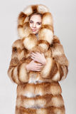 Portret van mooie jonge blondevrouw in de bontjas van de luxevos royalty-vrije stock afbeeldingen