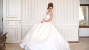 Portret van mooie jonge bruid Een meisje stelt in een hotelruimte De dame spint in haar huwelijkskleding stock videobeelden